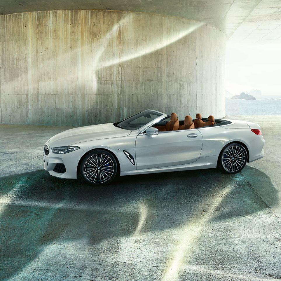 Nuova BMW M850i xDrive in Mineral White metallic, vista laterale con capote in tessuto aperta.