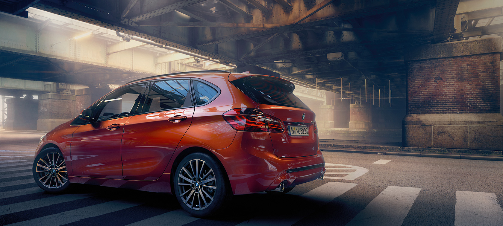 BMW Serie 2 Active Tourer F45 Facelift 2018 Sunset Orange metallizzato vista laterale da ferma in un padiglione