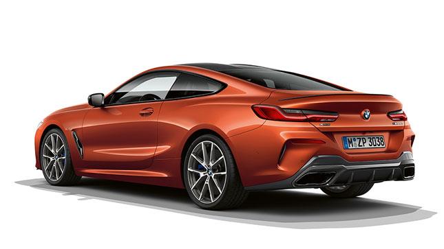 Ripresa da ferma della BMW Serie 8 Coupé in Sunset Orange metallizzato su sfondo bianco.