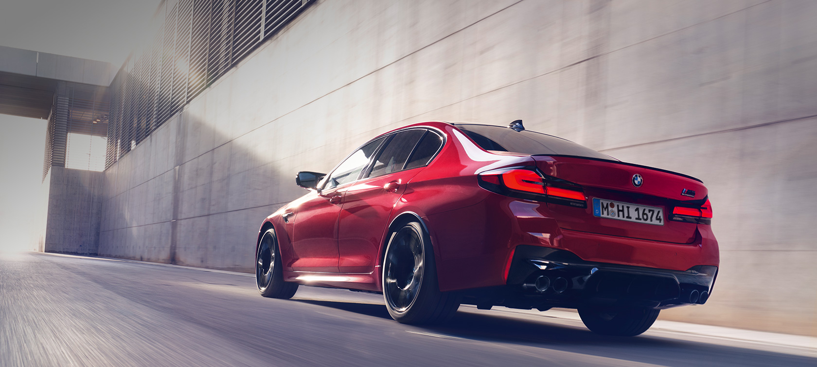 BMW M5 Competition F90 LCI Facelift 2020 BMW Individual Imola Red vista posteriore a tre quarti in movimento