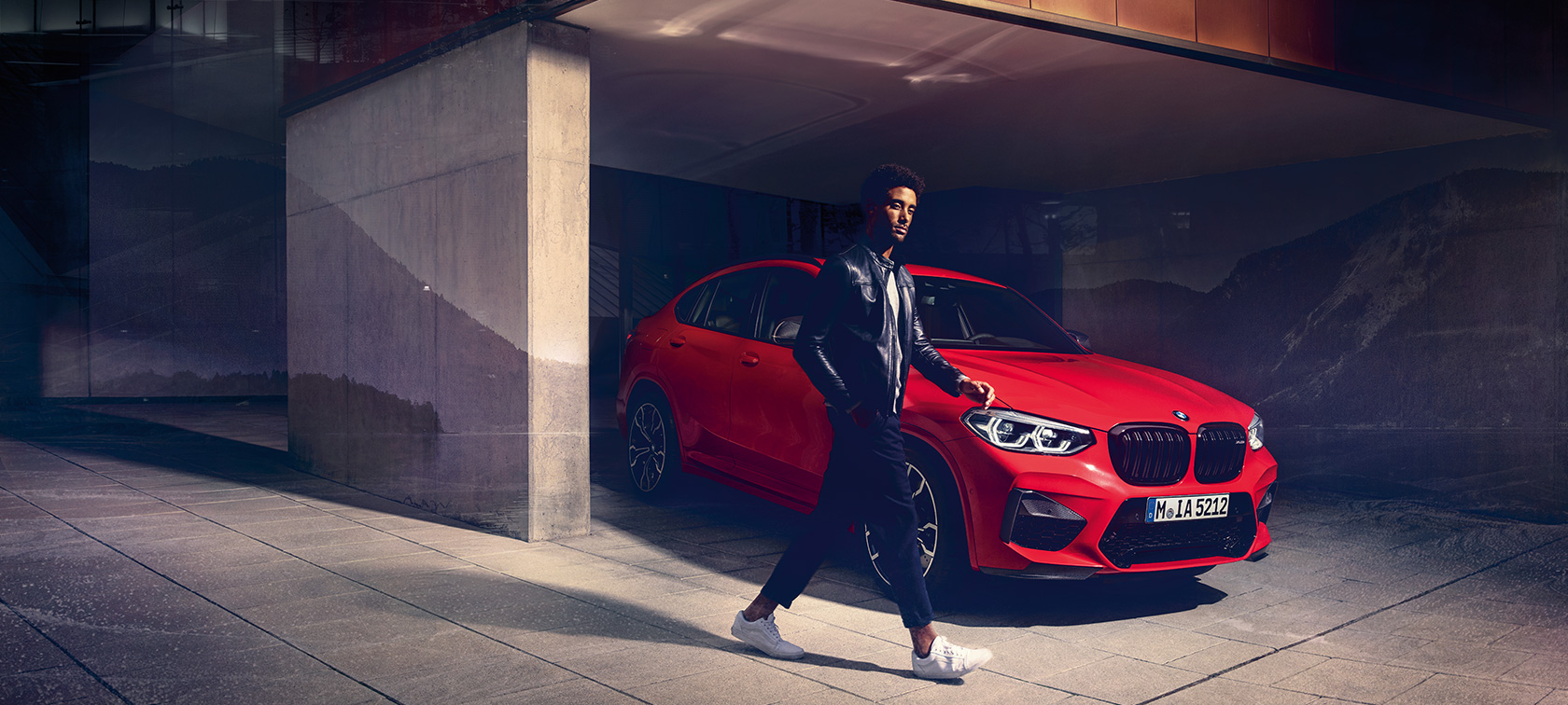 BMW X4 M Competition in Toronto Red metallizzato, esterni, vista laterale a tre quarti con ragazzo.