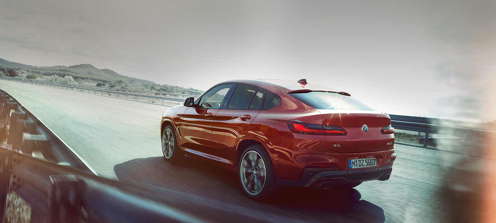 BMW X4 M40i G02 2018 Flamenco Red brilliant effect Red Vista tre quarti posteriorein movimento su strada