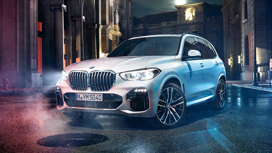 Immagine anteriore della BMW X5 di notte in ambiente urbano