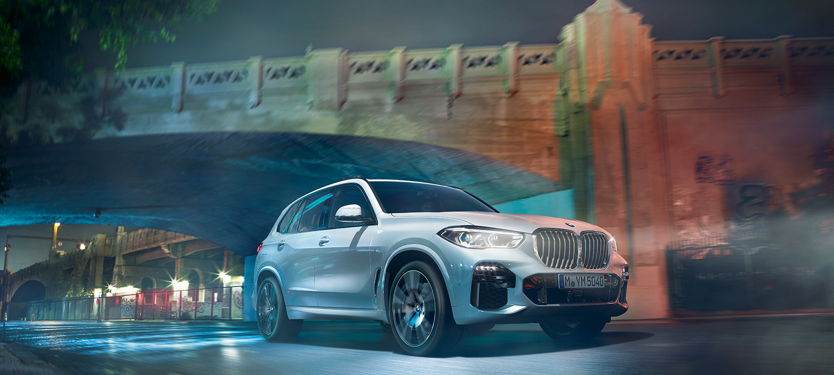 BMW X5 G05 2018 Mineral White metallizzato vista anteriore a tre quarti in movimento di notte